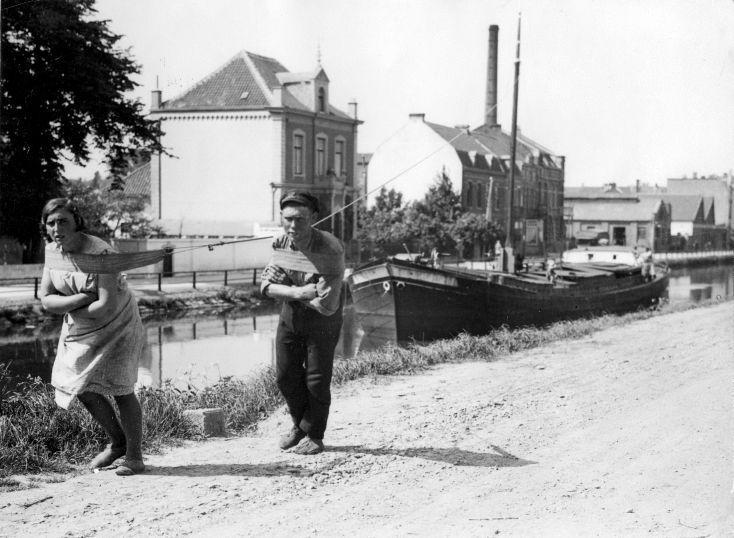 Een man en een vrouw trekken samen een trekschuit door een binnenkanaal. Plaats onbekend, 27 mei 1931.